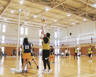 ネットボールは1チーム7人で行うスポーツ。バスケットボールと同じ高さのゴールにシュートが決まると1点。選手はポジションが書かれたゼッケンを着用する  =提供写真