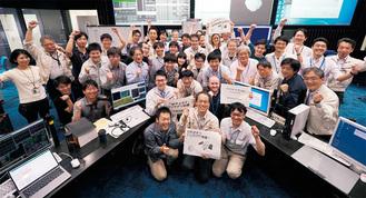 到着を確認し、ガッツポーズして喜びを表す管制室のスタッフたち=6月27日、JAXA(JAXA提供)
