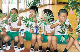 自ら製作した七夕飾りを笹に付ける園児たち=6月27日