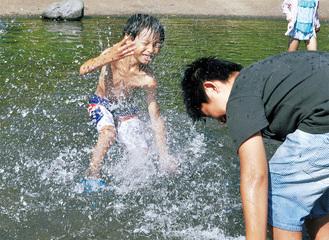 厳しい夏の暑さの中、水遊びを楽しむ子どもたち=19日、相模川自然の村公園