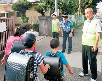 警察署員らに見守られ登校する児童=同校提供