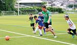 ボールを追いかける田中選手と子どもたち