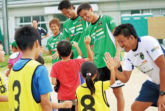 子どもたちとハイタッチを交わすSC選手とコーチら