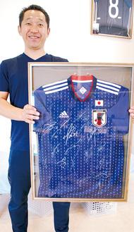 選手からプレゼントされたユニフォームを持つ久保田さん