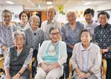 デイサービスの友人たちに囲まれ笑顔の芝田さん(前列中央)=13日