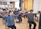 DVDを見ながら手の運動を実践する参加者=13日、すすきの自治会館