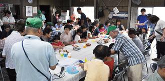 折り紙を一緒に楽しむ地域の高齢者と子どもたち