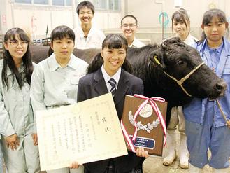 最優秀賞の賞状と盾を持つ宮崎さん(前列中央)と畜産部のメンバー。校内で飼育している牛と並んで=10月26日、相原高校