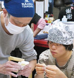 生徒と一緒に慣れた手つきで餃子を包む浅沼さん(左)