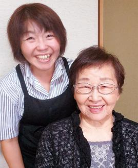施術後にさっぱりした利用者さんと一緒に笑顔を見せる関さん(左)