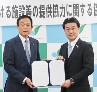 署名した協定書を持つ田中社長(右)と加山市長=12月25日、相模原市役所