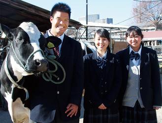 飼育する乳牛と並ぶ。左から角田さん、塗井さん、吉川さん=1月19日