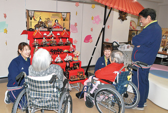 施設ロビーに展示されているひな人形に見入る利用者、スタッフたち=大野北誠心園