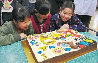 完成したケーキをうれしそうに眺める児童=19日、淵野辺東小学校