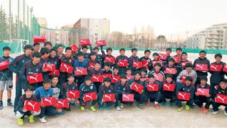 小林選手から贈られたスパイクを手にする同部の部員たち=同校提供