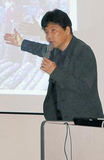 震災時に撮影した写真などを使って講演した佐藤さん=3日、相模原市民会館