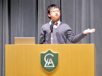 英語で堂々とスピーチをする児童=2月22日、LCA国際小学校