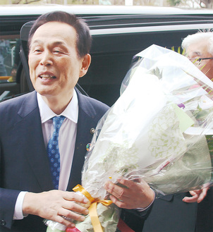 退庁時、詰めかけた市職員や市民に見送られ、花束を抱えて謝辞を述べる加山市長=19日、市役所正面玄関前で