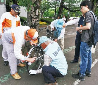 自転車を点検してもらいながら安全に利用するためのアドバイスを受ける市民=20日、市役所正面玄関前