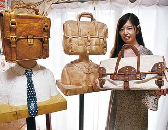 木彫りでできた作品を紹介する石山さん