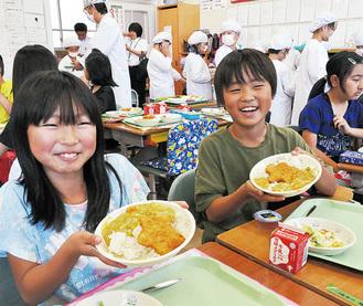 カレーを手に笑顔の児童=13日、田名北小
