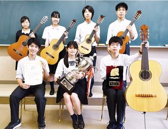 各自の楽器や表彰状、トロフィーを持つ上級生部員