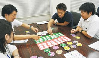 カードゲームを使ってSDGsを学ぶ市職員=8月、市役所