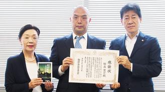 書籍を手にする静子さんと、感謝状を持つ寛行さん(中央)、野村教育長=9月18日、教育長室で