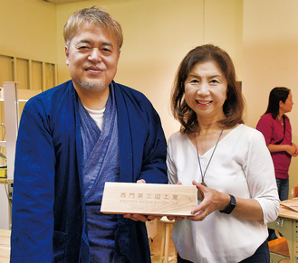 「MORIMO」の淵上美紀子代表理事(右)から開所記念の卓上看板を贈られた齊藤さん