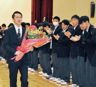 後輩から激励の花束をもらい、会場を後にする坂井選手=8日