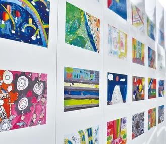 工事現場の仮囲いに展示されている児童の絵画=15日、橋本2丁目で撮影