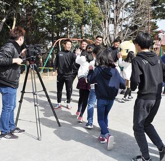 SCの選手らとハイタッチをする富士見小学校の児童たち