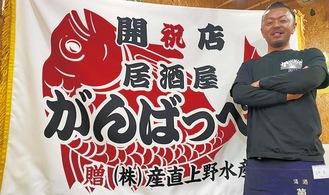 店名を記した大漁旗をバックに、店内で笑顔を見せる海宝プロデューサー=本人提供