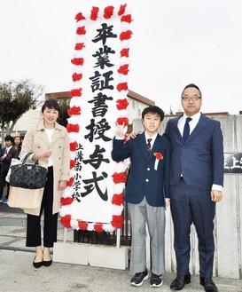 門出を祝い、校門の前で父母と一緒に笑顔を見せる拓さん=23日、上溝南小学校