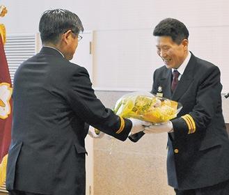 就任祝いの花束を受け取る原さん(右)