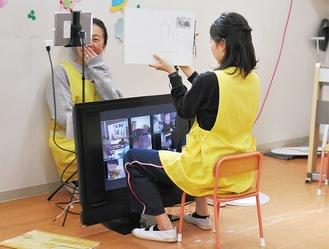 子どもたちが映る画面に向かって紙芝居の読み聞かせをする教諭=17日、田名幼稚園