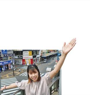 淵野辺駅北口デッキからの界隈を背景に笑顔のイバ