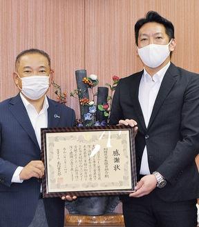 感謝状を受け取った木村執行委員長(右)と本村市長