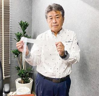 神奈川県に寄付したフェイスシールド手にする黄木会長=提供写真
