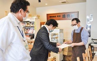 参加希望店舗から書類を預かる鈴木崇之上溝商店街振興組合理事長(中央)