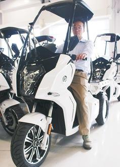 同社の3輪電動スクーターに乗る担当者