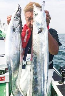 釣りあげた魚を掲げる望月さん
