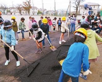 校庭で敷きならしの体験を行った児童=11月12日、田名小学校