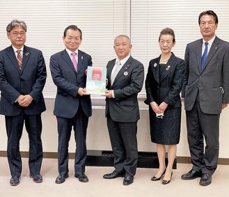 設立30周年記念誌を本村賢太郎市長に渡す板橋理事長(左から2番目)=6日