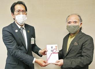 目録を手渡す江成さん(右)と鈴木教育長