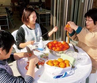 仮設住宅時代から世話になった住民らと一緒に干し柿を作る中村さん(中)=キャッセン大船渡