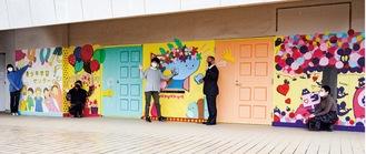 ウォールアートの完成を喜ぶ(左から)山下さん、山本幸奈さん(多摩美術大学2年)、川口友綺さん(同)、本村賢太郎市長、前川さん=8日、青少年学習センター