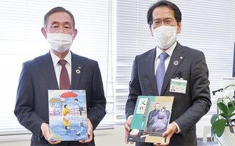 図書を受け取る鈴木教育長(右)と曽我専務理事