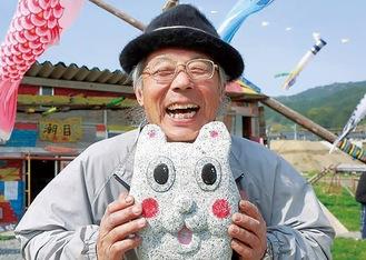 震災資料館「潮目」を前にとびっきりの笑顔を見せる片山さん