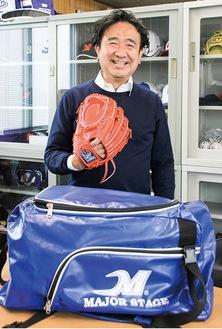 自社ブランド「メジャーステージ」のグローブとバッグを紹介する村田社長=13日
